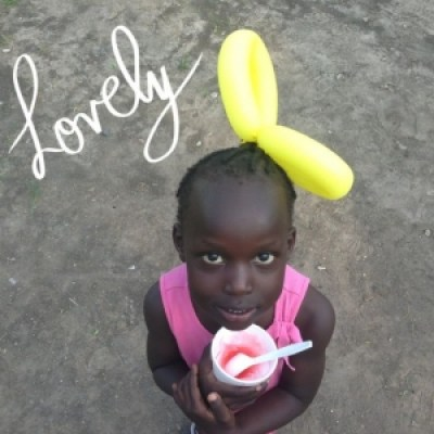 Young child wearing a balloon hat and eating frozen yogurt