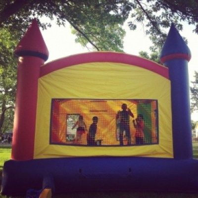 Large bouncy house being enjoyed by kids.