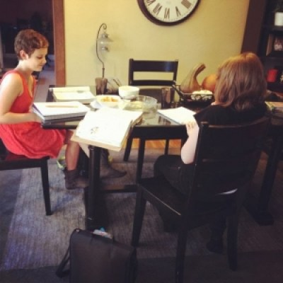 girls doing homework at dining room table