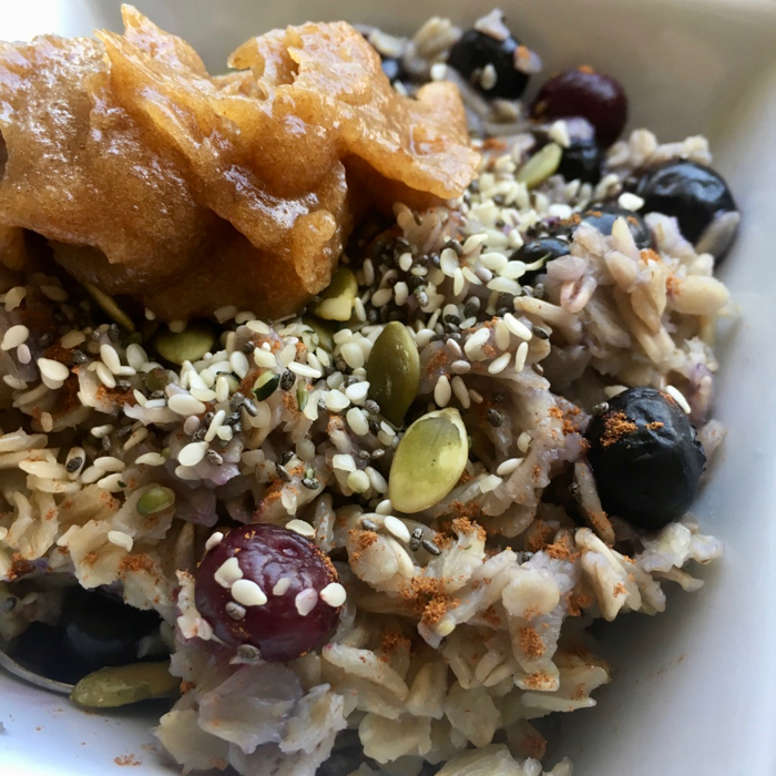 bowl of oatmeal topped with seeds and date paste