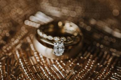 Gold with oval diamond engagement rings on gold bead background