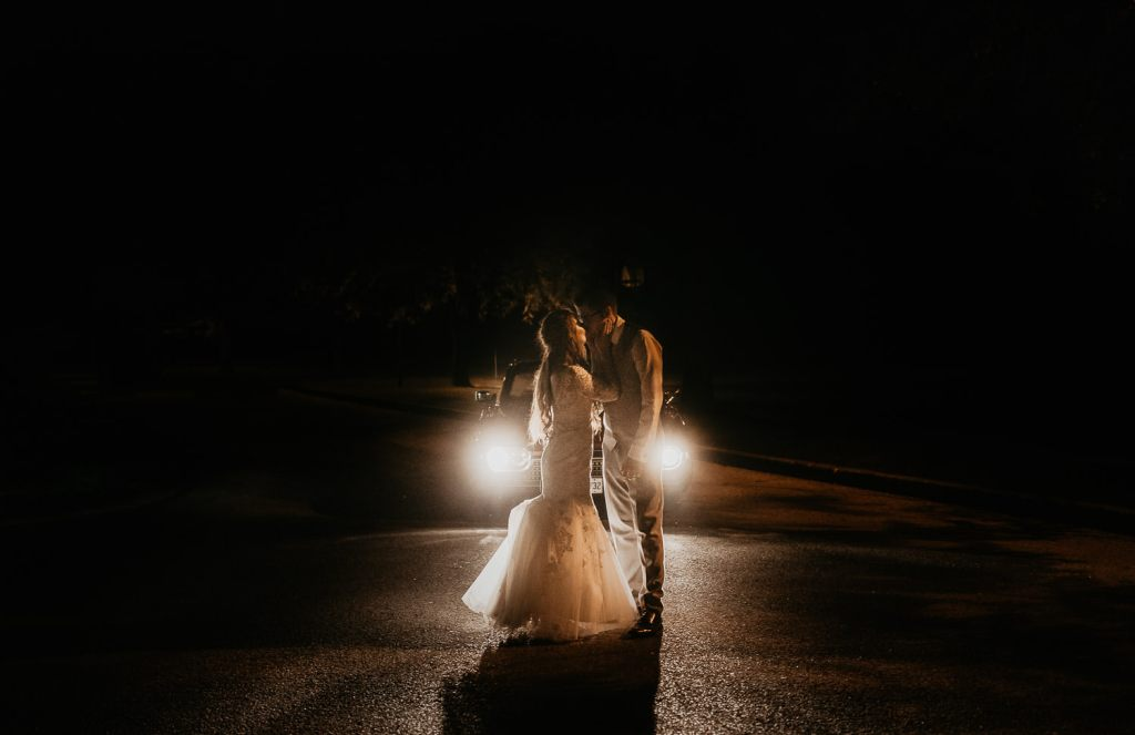 Wedding couple standing in front of car headlights