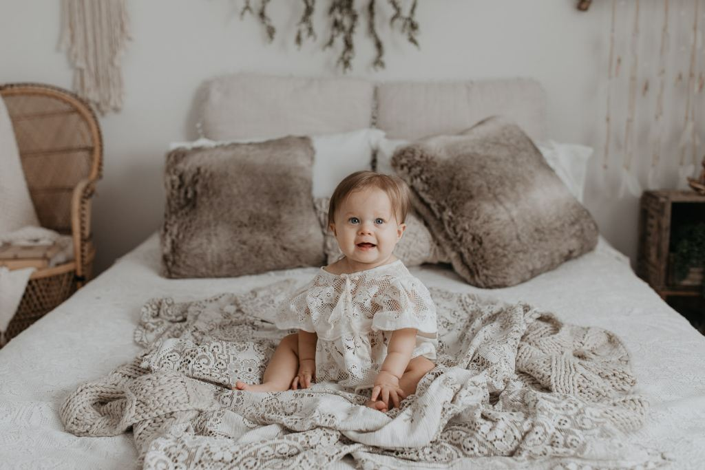 baby sitting on bed