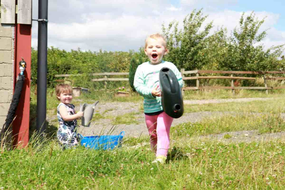 two little girls playing with watering cans and a horse bucket
