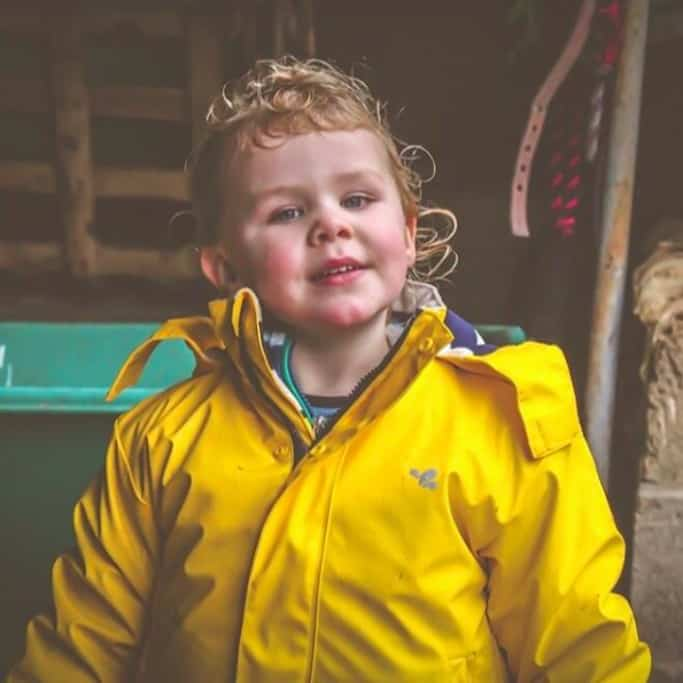 A toddler in a bright yellow jacket visiting her horse yard