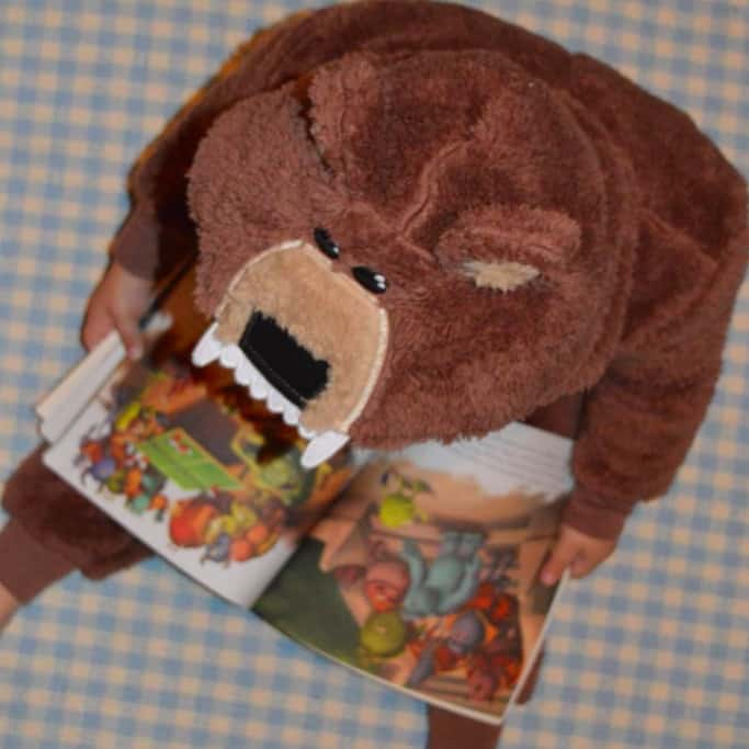Aerial view of a toddler reading a book dressed in a bear costume!