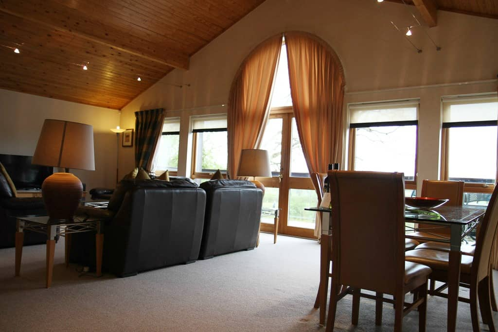 Upside down living at Belton Woods Q Lodges, Lincolnshire. The lounge with huge sofas, dining table and TV with freeview
