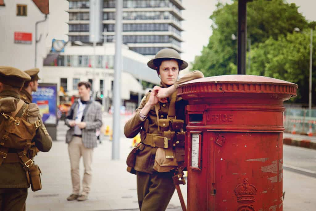 A young man dressed as a soldier leans against a red telephone box. The soldiers each depict a man that lost their life in the Battle of the Somme.