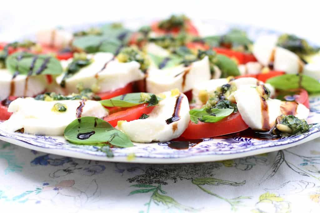 A tricolore salad using tomatoes, mozzarella, basil with homemade pesto and a coca-cola zero sugar reduction