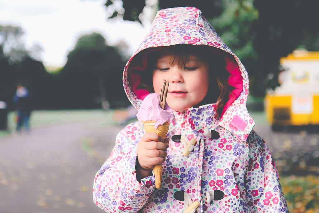 Toddler eating an ice cream in the rain wearing Jo Jo Maman Bebe raincoat