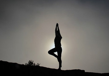A silhouette of a woman standing in a tree pose, outdoors on uneven ground, arms overhead, yoga classes Boston..