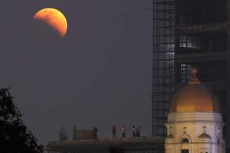 EPA2042. CALCUTA (INDIA), 31/01/2018.- Varias personas observan el eclipse lunar total cerca de un edificio histórico en Calcuta (India) hoy, 31 de enero de 2018. Millones de personas en más de la mitad del mundo podrán ver hoy cómo la Luna se tiñe de color rojizo debido a un eclipse lunar total, que además ocurre con el satélite en su punto más cercano a la Tierra. EFE/ Piyal Adhikary