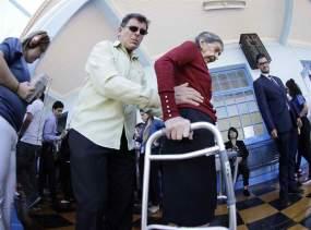 Una persona de la tercera edad es ayudada cuando acudió a votar/Foto: EFE