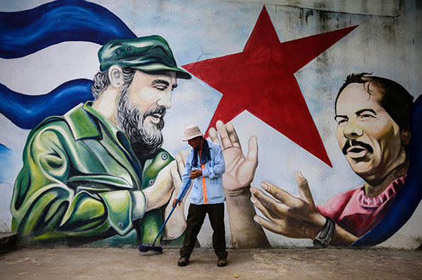Η πρώτη εγκόσμια θρησκεία TOPSHOT - A municipal worker sweeps the floor in front of a mural depicting Cuban revolutionary leader Fidel Castro (L) and Nicaraguan President Daniel Ortega at Cuba square in Managua on November 26, 2016, the day after Castro died. Cuban revolutionary leader Fidel Castro has died aged 90, prompting mixed grief and joy Saturday along with international tributes for the man whose iron-fisted rule defied the United States for half a century. / AFP PHOTO / INTI OCONINTI OCON/AFP/Getty Images