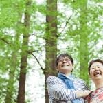 内田かつのり先生と60代女性がもりの中で笑顔で空を見上げている様子