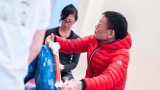 ヨガ解剖学講師内田かつのり先生の膝関節セラピー。生徒さんの腿に骨模型を載せて説明する内田先生
