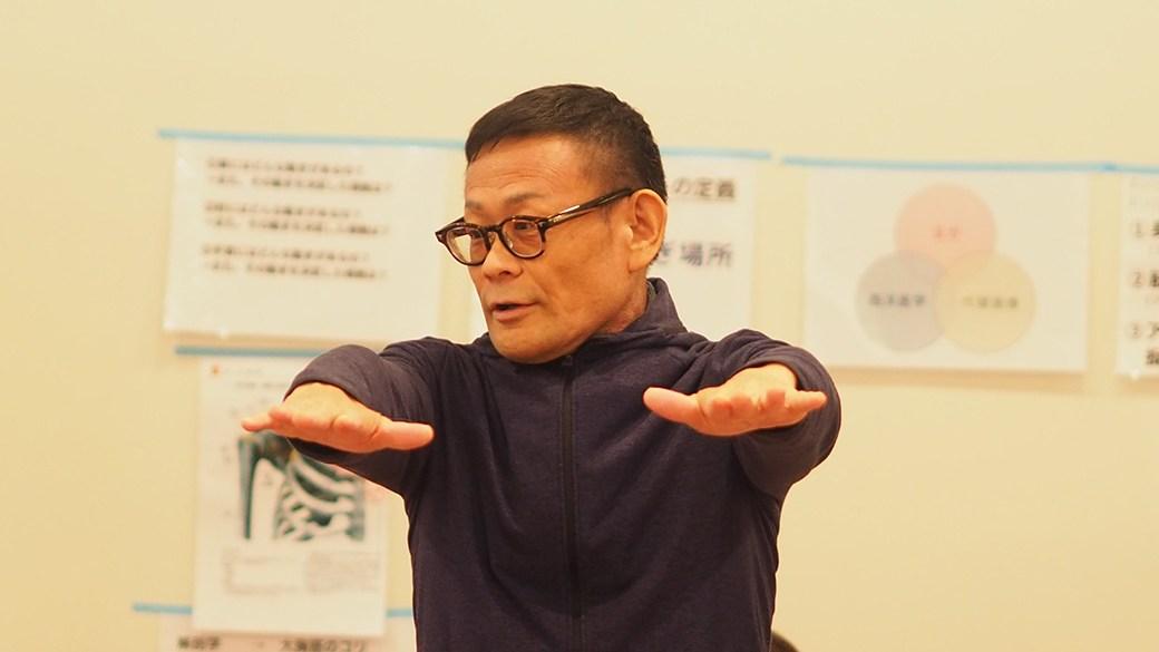 内田先生が手のひらを下にして両腕を地面と平行に上げている様子