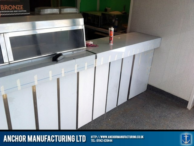 Chip shop stainless steel counter with cladding.