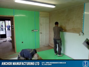 Shop fitters install wall cladding.