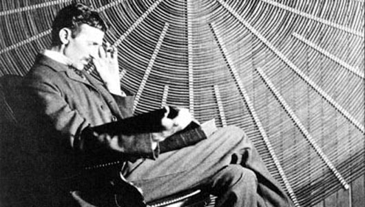 An image of Nikola Tesla sitting and reading in front of a spiral coil of his high-voltage transformer.