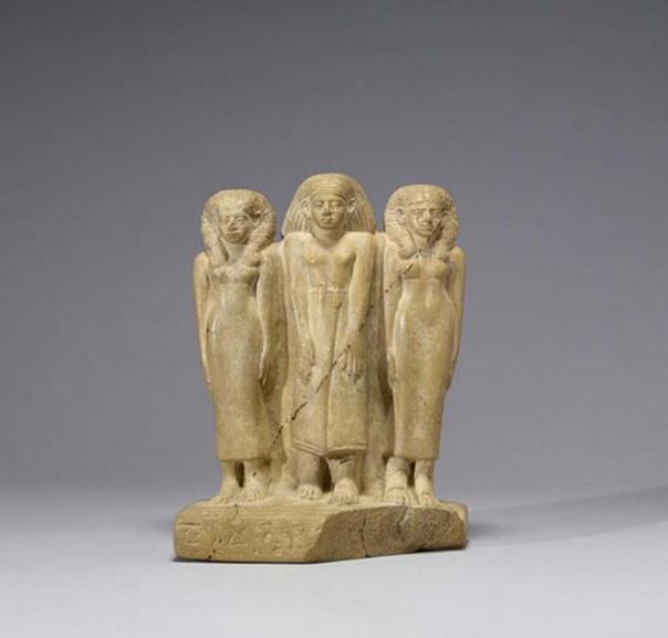 Grupo familiar, estatuilla de piedra caliza en la que se observa a un hombre en el centro, flanqueado por dos mujeres. Imperio Nuevo (c. 1850-1800 a. C.) (Public Domain)