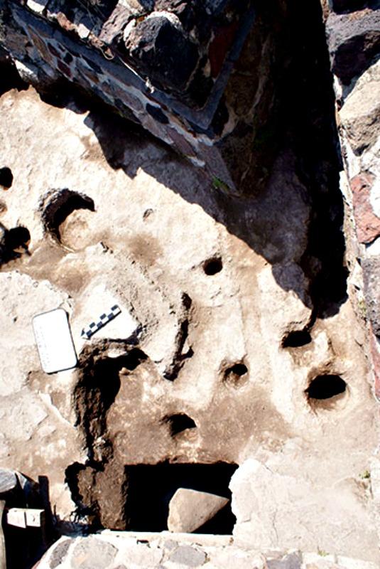 Algunas de las oquedades en el tepetate y una de las fosas con estela verde en el flanco sur de la Estructura A. (Fotografía: Proyecto Estructura A, Plaza de la Luna, Teotihuacán, INAH)