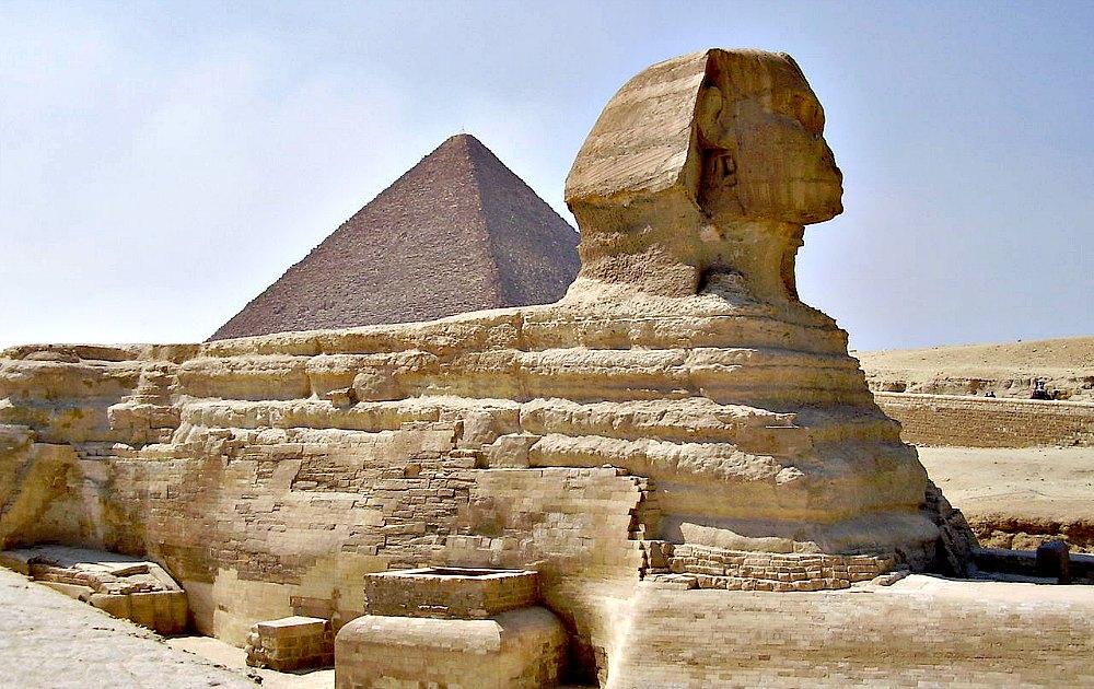 Portada - Vista lateral de la Gran Esfinge de Guiza con la Gran Pirámide al fondo. (GNU Free)