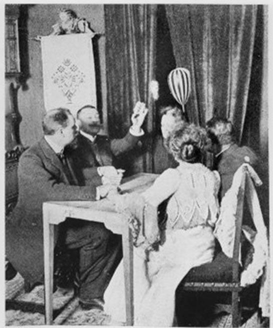 La mandoline (instrument rayé, en haut, à droite) lévite au-dessus de la tête de Palladino devant les rideaux à l'extrémité très courte de la table pendant la séance de Palladino à Munich, Allemagne, le 13 mars 1903.