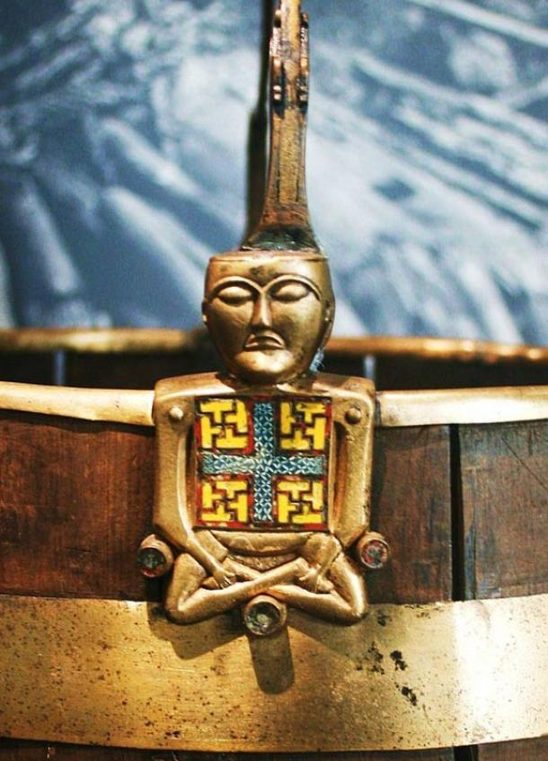"A curious artifact, the so-called ""Buddha bucket"" (Buddha-bøtte), a brass and cloisonné enamel ornament of a bucket (pail) handle in the shape of a figure sitting with crossed legs.  It is thought this item likely came from Ireland, and might have been taken during a raid."