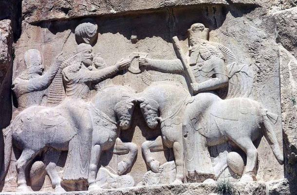A relief at Naqsh-e Rustam in modern-day Iran showing Ardashir I and an unidentified cavalier. This Persian rock relief depicts Ardashir I's coronation scene, as the first king of the Sassanid Empire of Iran. Ardashir I receives the cydaris ring of power, the Zoroastrian symbol of kingship, from the spirit of Darius the Great of the Achaemenid dynasty. The inscription in Persian, Parthian, and Greek, reads: This is the image of the Hormizd-worshipping Majesty Ardashir, whose origin is of the gods. (Ginolerhino 2002 / CC BY-SA 3.0)