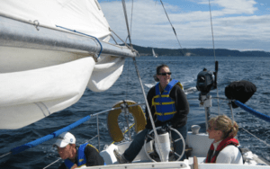 Devon at the helm while sailing with double reef in the main