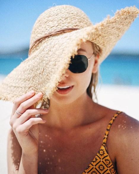 occhiali da sole e cappello in spiaggia