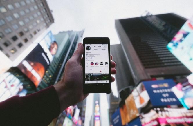Uomo con smartphone in mano mostra Instagram