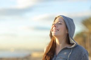 Frau lacht in die Sonne