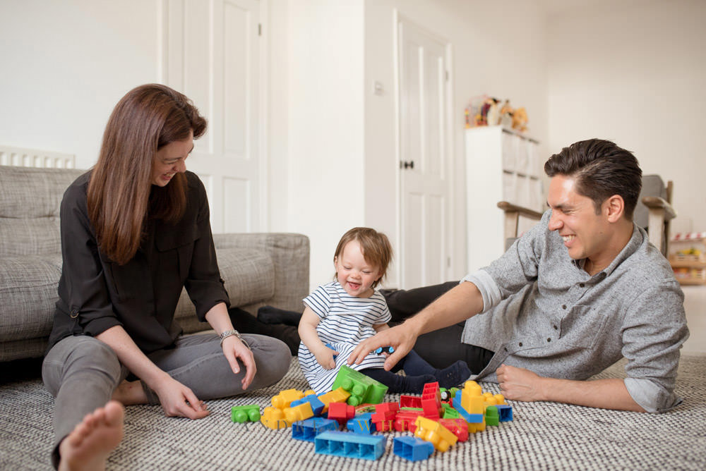 Mum and Dad playing with baby at home