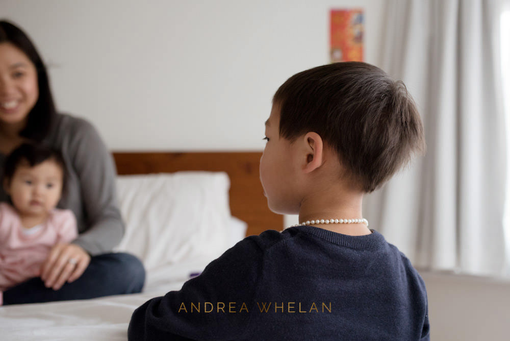boy wearing mothers necklace