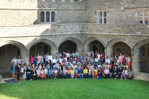 A diverse group of ~100 graduate students and professors, all wearing business casual attire, pose for a photograph in several rows. Some are standing and some seated. In the foreground is a grassy lawn, in the background are the columns and arches of a cloister at a collegiate-gothic style building.