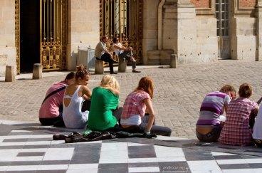 Молодежь отдыхает на ступенях Версальского дворца.