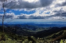 Дождевые облака над холмами, и озеро Аренал на заднем плане.