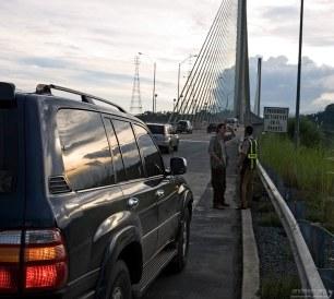 Илья разговаривает с полицейским на мосту через Панамский канал.