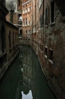 Отражения домов в спокойных водах канала.