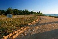 """Дорога на полуострове Плаценсия, она же посадочная полоса. Надпись на знаке: """"дай дорогу взлетающему или садящемуся самолету"""". Южный Белиз."""