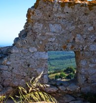 Оливковые поля через амбразуру в крепостной стене замка Chlemoutsi.