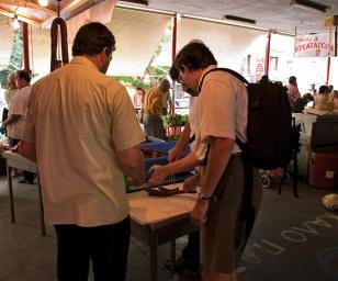 Илья покупает копченую сосиску на рынке в Каламате.