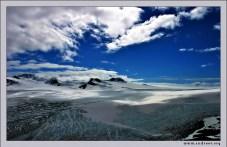 """""""Аляска подо льдом"""". Огромное ледовое поле Harding Ice field высоко в горах Kenai Mountains. Добраться туда можно только в июле-сентябре, 15 км туда-обратно по горам. Все остальное время путь покрыт толстым слоем льда и снега. Отсюда же берет начало ледник Exit Glacier, спускающийся с гор синим языком, и испещренный моренами. Многометровые слои льда с расщелинами выглядят довольно устрашающе, но в то же время притягивают насыщенным голубым цветом."""
