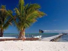 Пирс, вдающийся в зеленые воды Карибского моря.