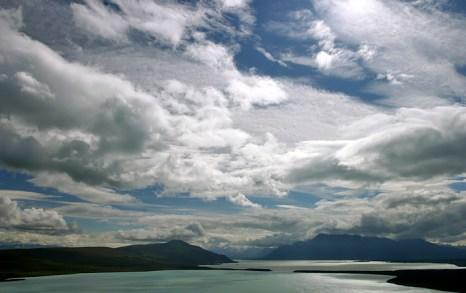 Облака над сине-зеленой водой озера Naknek lake.