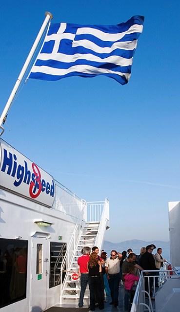 Пассажиры парома и греческий флаг.