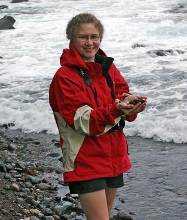 Катя с красным песком в руках.
