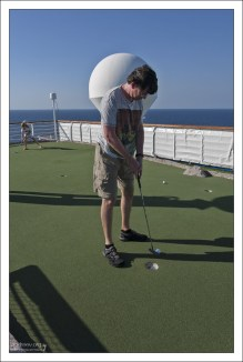 Илья и Саша играют в мини-гольф.